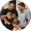 Jófejség a négyzeten: egymást tanítják az apukák copfot kötni!
